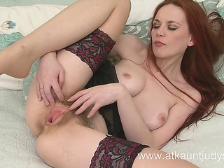 Mistique fingers her moist in addition to furry pussy